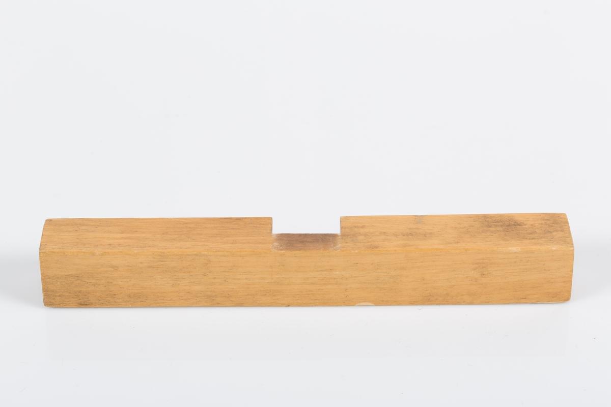 Del av kors i lakert tre. Horisontal del til trekors som består av to deler. Delen har kvadratisk snitt. På midten er det skåret ut et firkantet snitt for innfelling av korsets vertikale del.