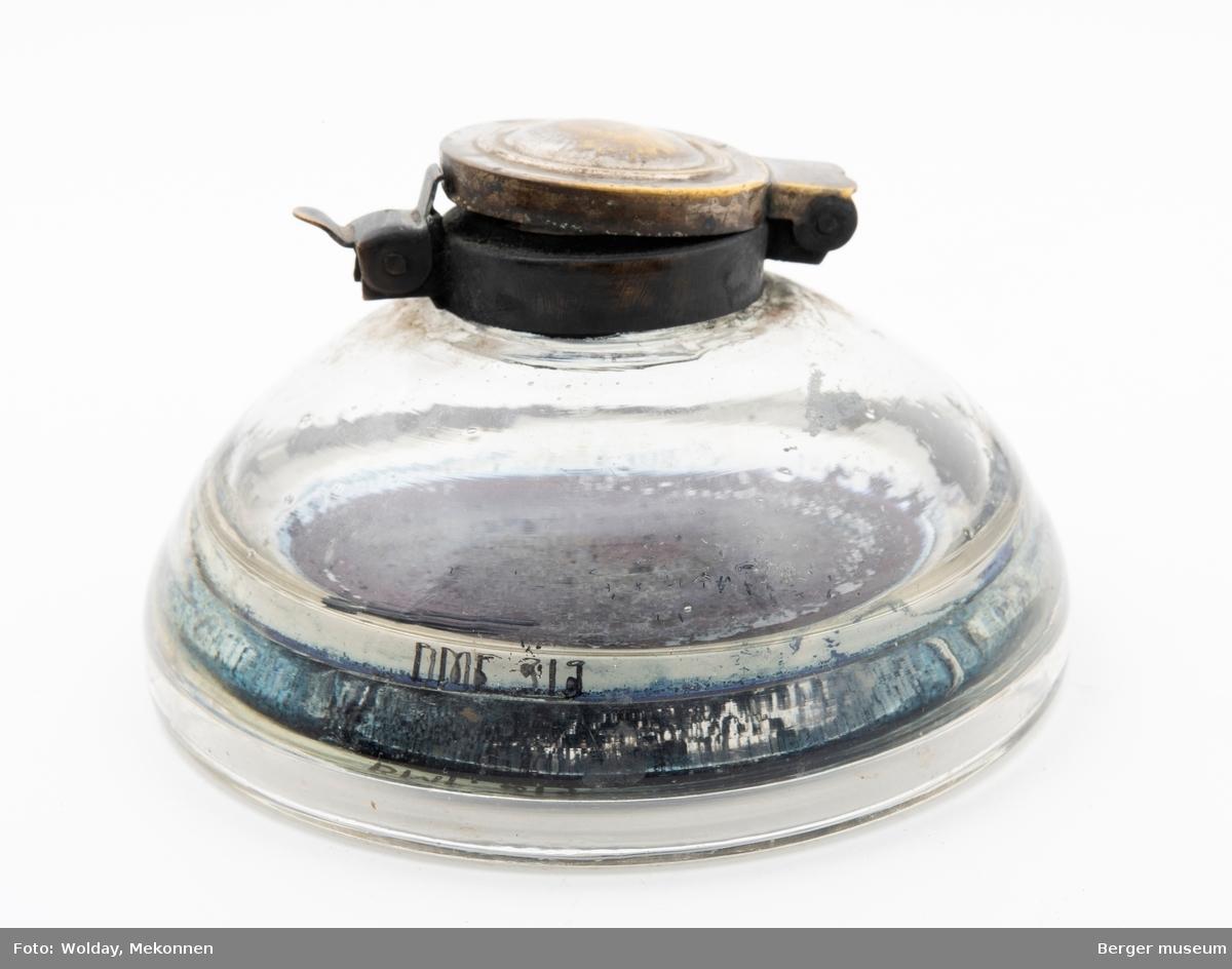 Rund, flattrykt glassbeholder med lokk i metall. Blekkrester i bunnen.