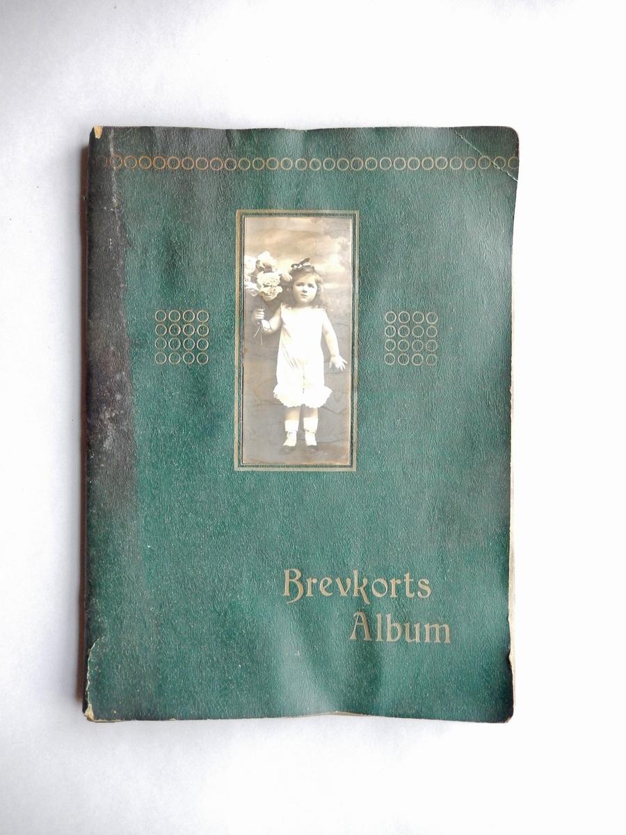 Brevkortsalbum med omslag av grön papp och tryck i guldfärg samt fotografi av en liten flicka i underkläder med en blombukett i handen. Gråbruna blad med skåror för att sticka in vykort. Tre lösa kommersiellt framställda fotografier föreställande små skulpturer.