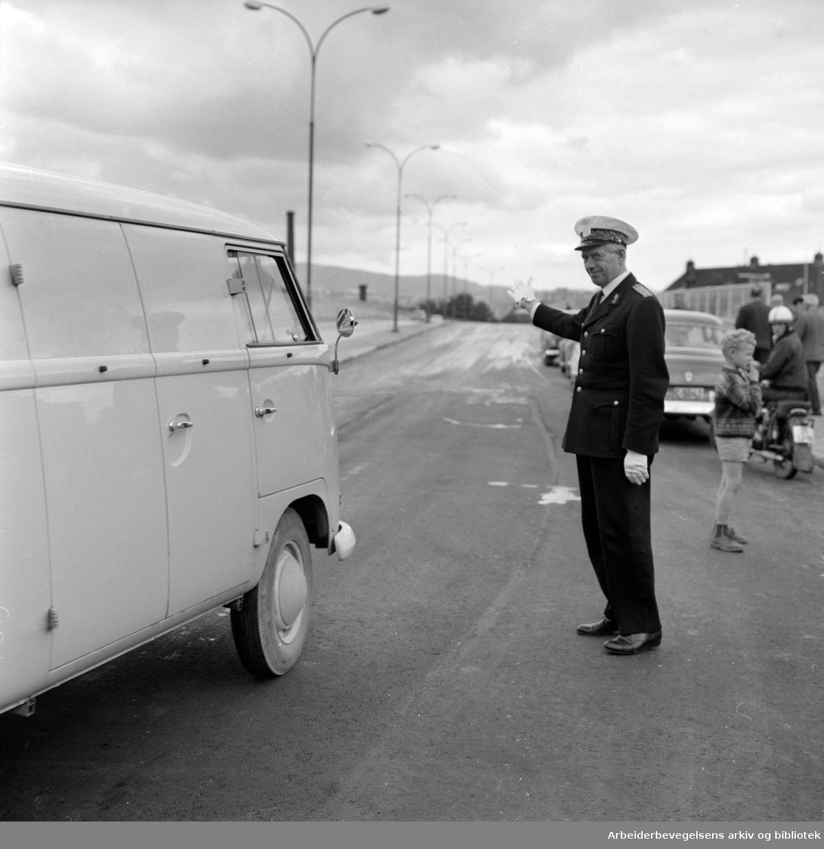 Loengbrua åpnet for fullt. Trafikkinspektør Thorleif Karlsen vinker den første bilen over. Juni 1963