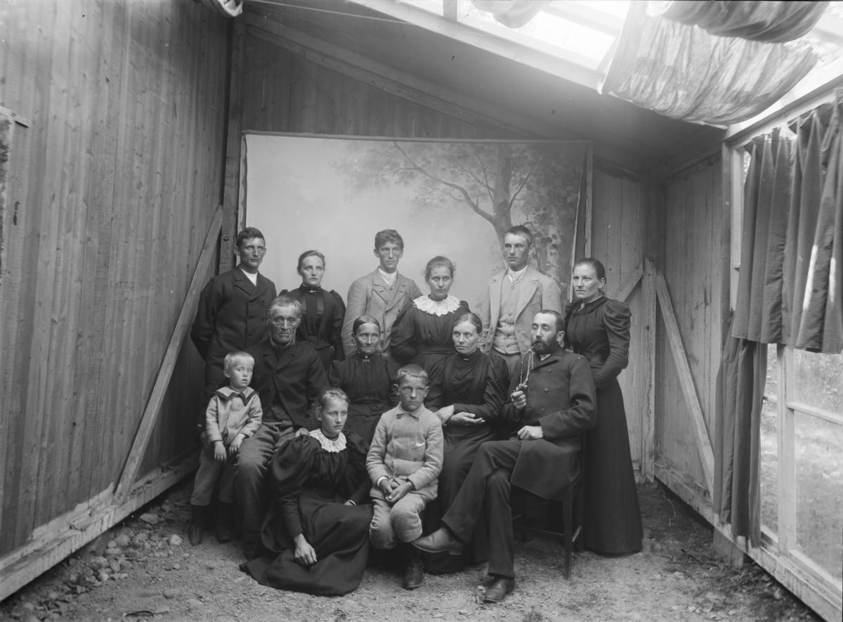 Familiebilde med 13 personer og tre generasjoner. Atelierfoto (provisorisk ved reisverksbygning) fra Gudbrandsdalene eller sidedalene i tidsrommet 1890-97