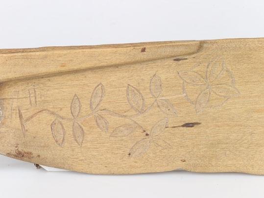 Anmärkningar: Skäktträ av trä, ek. Handtag och blad. Efter bladets rygg en från handtaget löpande till halva bladets längd gående förstärkning. Bladets översida ornerad med en naturalistiskt skuren gren med blad och en fyrkantig blomma inom en cirkel. Enligt Liggaren köpt för 0,5 kr 1875.