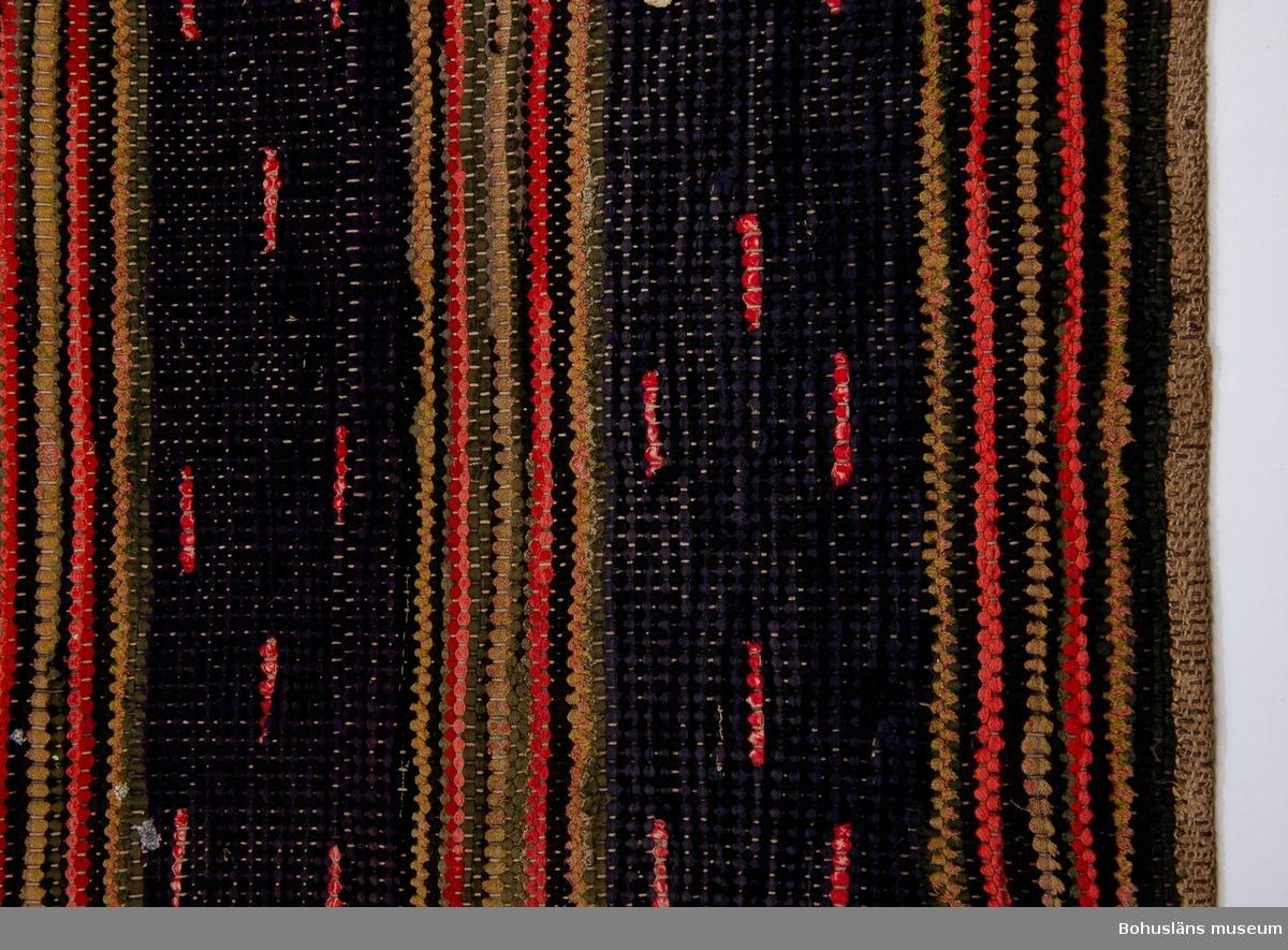 Dekorativa röda och vita cirka 4 centimeter långa trasbitarna är plockade in i de skyttlade inslagen. Observera att det är baksidan som fotograferats.