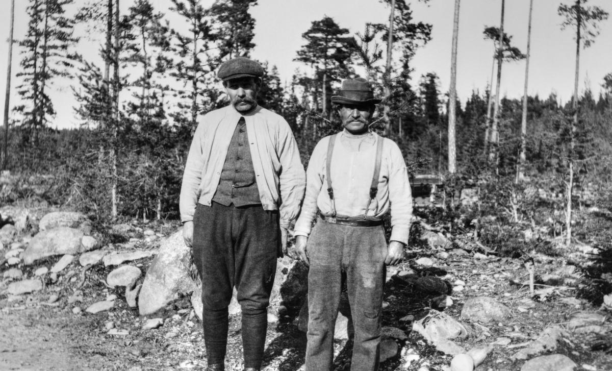 Portrett av tømmerfløterne Per Vangli (til venstre) og Per Øien fra Nordre Osen i Åmot kommune i Hedmark.  Disse to karene drev småskalajordbruk om sommeren, arbeidde i tømmerskogen om vinterenm og fløtte tømmer i elva Søndre Osa i vårsesongen.  Her er de fotografert ved en vegkant med en furumo i bakgrunnen, antakelig i hjemtraktene.  Per Vangli var kledd i vadmelsbukser med puttiser på leggene.  På overkroppen hadde han busserull, der bare den øverste knappen (i halslinninga) var kneppet.  Under busserullen later det til at han hadde et vestliknende plagg.  På hodet hadde Per Vangli såkalt sixpencelue, altså ei bomullslue med skjerm som kastet skygge over panna og øynene.  Arbeidskameraten Per Øien hadde bukser som var lappet på lårene og knærne, og som ble holdt på plass både av belte (livreim) og bukseseler.  På overkroppen hadde han ei lys bomullstrøye, og på hodet bar han en hatt.  Per Vangli og Per Øien fikk heltestatus våren 1916.  Den 10. mai dette året sviktet den halvannet år gamle kraftverksdammen ved Osfallet i Søndre Osa under en brå og kraftig vårflom da damkarene ikke greide å få åpnet lukene som skulle brukes til å lette trykket på konstruksjonene i slike situasjoner.  Konsekvensen ble at elva brøt igjennom grusmassene i den nordre damarmen, og grov seg et nytt løp, der vannmassene førte med seg grus, stein og trær som strømmen hadde vasket løs.  Det nye løpet gikk rett mot kraftverkets maskinistbolig, der maskinist Karl Haag og hans mor oppholdt seg.  Bygningen ble liggende midt i et strømkav, og da maskisten åpnet døra for å berge mora og seg sjøl over på noe som framsto som et skjær like ovenfor bygningen, kollapset første etasje i bygningen, og mora ble klemt fast under en bjelke.  Per Vangli og Per Øyen fikk greie på hva som hadde skjedd, og fikk fraktet en fløterbåt ned til Osfallet ved hjelp av en hest.  Tidlig på formiddagen 11. mai 1916, dagen etter dambruddet, tok de seg over til maskinistboligen i denne farkosten.  Mens de hogg istykker b