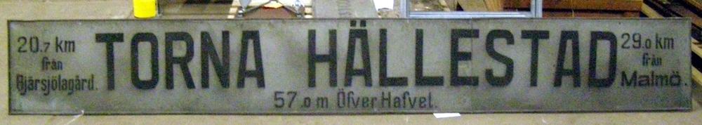 """Rektangulär skylt av metall med svarta bokstäver som anger ortsnamnet Torna Hällestad samt """"20.7 km från Bjärsjölagård 29.0 km från Malmö"""". Från tidigare insamling. Utan vidare proveniens. Torna Hällestad station längs linjen Dalby-Harlösa-Bjärsjölagård, öppnade 1910. Uppgift från föremålsliggare: """"Stationsskylt från Torna-Hällestad å f.d. Dalby-Björsjölagård 28 Bö Ystad!  Tillägg 2010-09-30_MW: Efter kontakt med Torna-Hällestads byalag under våren år 2010 har Järnvägsmuseet fått två bilder av fotografier på stationshuset Torna-Hällestad där skylten sitter uppe,  samt informationsblad framtagna i samband med jubileumsfirandet: """"Järnvägen Torna Hällestad 100 år, år 2010"""", till detta jubileum har man i Torna Hällestad gjort en exakt kopia av skylten som fått en permanent placering utomhus på det gamla stationsområdet och originalskylten lånades även ut till jubileumshelgen den 18-19 september år 2010, informationsblad och bilder ligger som bilaga till föremål Jvm8755:1. Se även Dnr: 10-50."""