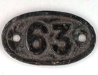 """Oval skylt av svartmålad mässing med text i relief: """"63"""". Från ångloket EHRJ 3  SWB 63 (1914) SJ KA8 1686 NOHAB Nº 770."""