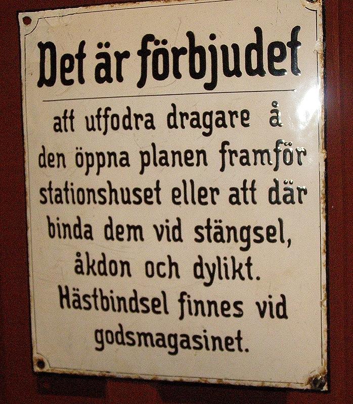 """Vit plåtskylt med blå text: """"Det är förbjudet att utfordra dragare å den öppna planen framför stationshuset eller att där binda dem vid stängsel, åkdon och dylikt. Hästbindsel finnes vid godsmagasinet."""""""