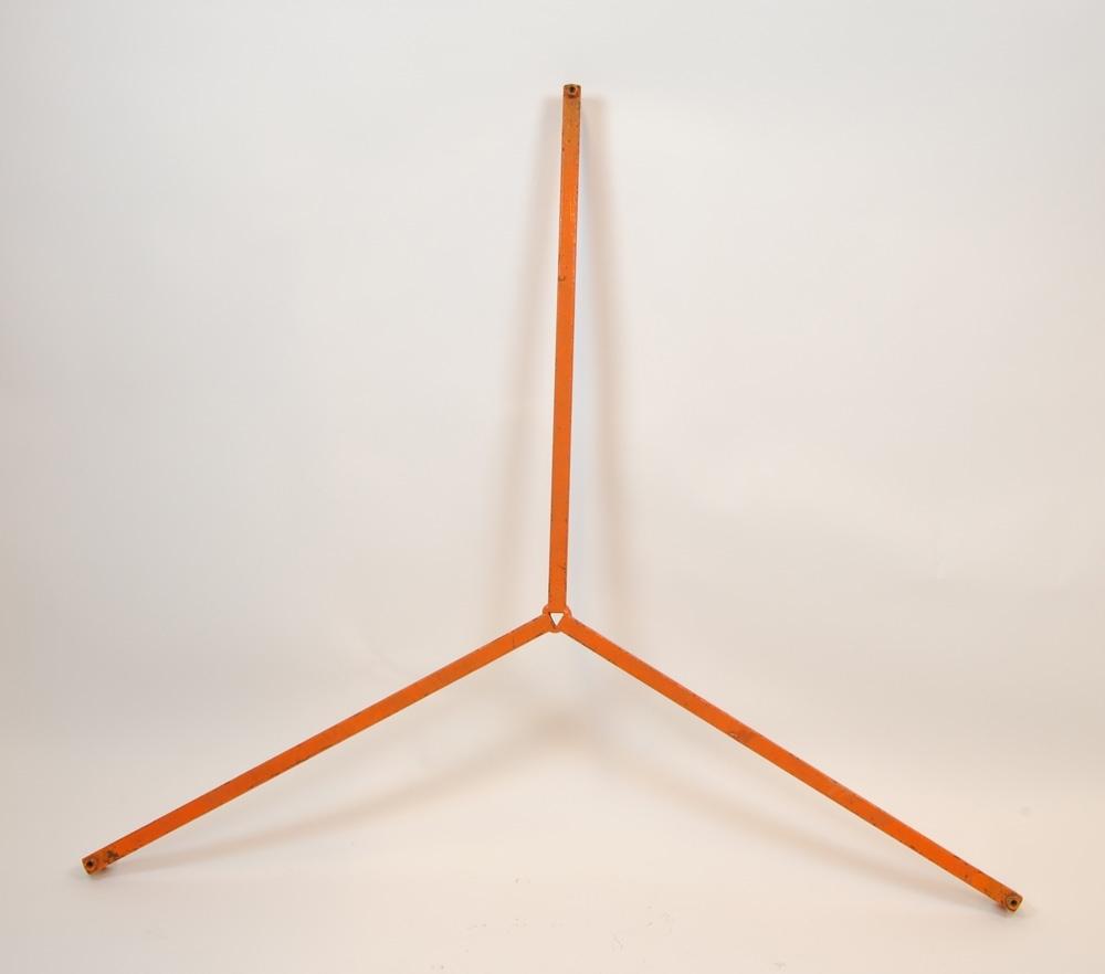 Trefot av metall med hål för att ställa stativben i. Trefoten är målad orange.