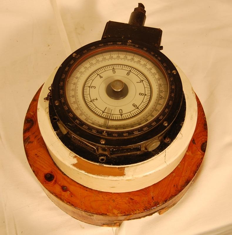 Gyrokompass som använts på en av SJ:s färjor, okänt vilken. Kompassen är fastskruvad på en vitmålad träcylinder. Den vitmålade träcylindern har i sin tur varit fästad i en lackad träcylinder, nu ligger den löst ovanpå.