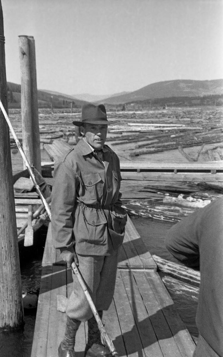 Oppsynsmann Wethe ved Lillehammer lense, fotografert på en av flåtegangene ved lenseanlegget.  Bildet ble tatt i 1952.  Wethe hadde vindjakke på overkroppen, nikkersbukser på beina og filthatt på hodet.  I den ene handa holdt han en langskaftet fløterhake, som ble brukt under sortering etter eiermerker på tømmerstokker og når stokkene skulle sendes ned til mosemaskinen (soppeapparatet) som buntet tømmeret med tanke på buksering over Mjøsa.
