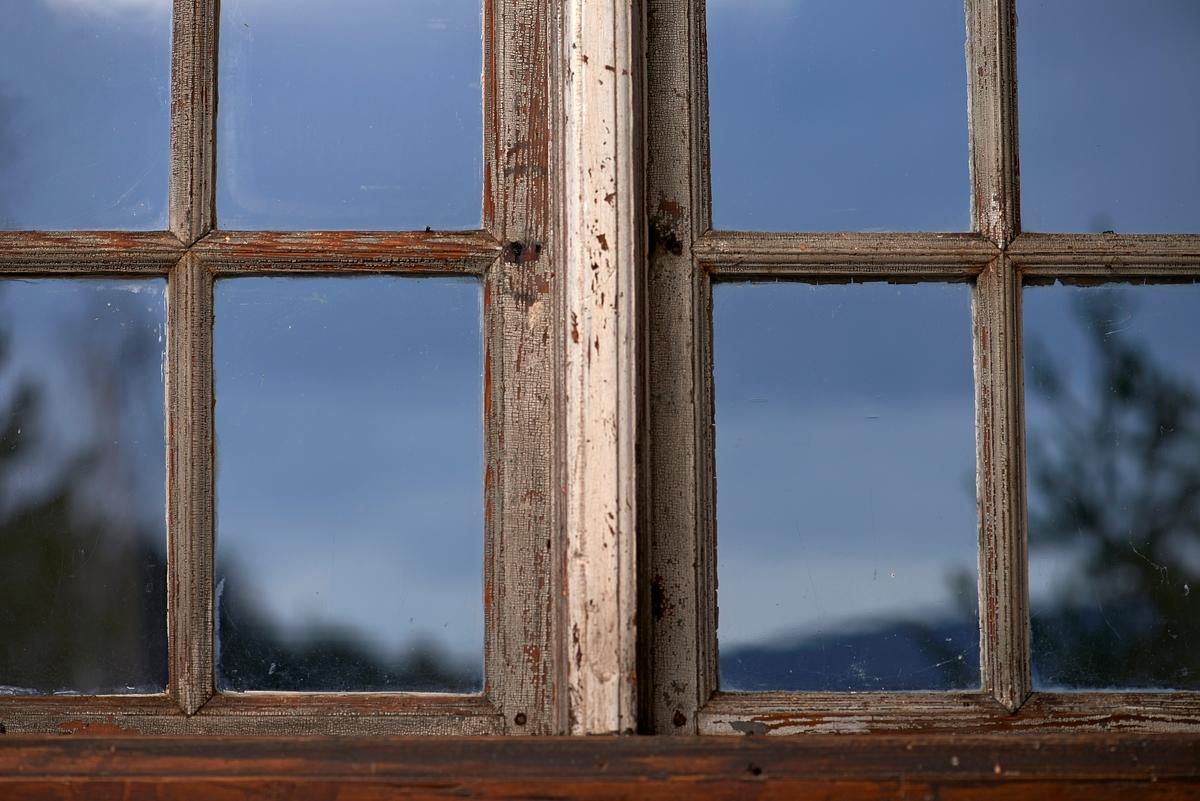 Detalj fra vindu i «Austmostua» eller «Østmostua» på Glomdalsmuseet i Elverum.  Denne bygningen er egentlig fra Mogrenda på Vestsida i Hoff i Solør, men den ble flyttet og gjenreist på museet i 1919.  Fotografiet er tatt mot den nedre delen av et vindu med to grinder, som her møtes ved en profilert vertikal midtpost.  Vindusrammene er av den klassisistiske typen, som ble vanlig mot slutten av 1700-tallet og fortsatt ble brukt et godt stykke utover på 1800-tallet.  Så vel rammetrærne som sprossene er bearbeidet med profilhøvel.  Disse trekomponentene ser ut til å ha vært innsatt med ei grålig maling, som er delvis vekkslitt.  Midtposten har tilsynelatende en annen og sannsynligvis nyere malingstype.  Vinduet ser ikke ut til å ha hasper.  De kunne med andre ord ikke åpnes.    Austmobygningen (jfr. SJF-F. 006768) er en 10, 7 meter lang og 9 meter bred laftet svalgangsbygning med torvtekket saltak.  Første etasje har såkalt akershusisk grunnplan med inngang til et stuerom med dører videre til to mindre rom, et kjøkken og et kammers i den andre enden av bygningen. Annen etasje er delt i to rom, som har separate dører mot svalgangen.  Den bæres av dreide stolper.  Oppgangen til annen etasje skjer via ei trapp med repos i den ene enden av svalgangen.  Ved denne trappa er bygningen delvis borkledd.  I motsatt ende av svalgangen i annen etasje er det også en bordvegg, antakelig fordi det var et kott der. Museumsmennene Håvard Skirbekk og Hilmar Stigum konstaterte at huset ikke hadde vært slik det framstår på museet bestandig.  Skirbekk bad dendrokronologipioneren Sigurd Aandstad om å datere tømmeret.  Han kom til at veggstokkene i første etasje var hogd i 1730.  I annen etasje har laftinga et annet preg.  Både Skirbekk og Stigum var derfor enige om at dette var ei akershusisk stue som var blitt påbygd en etasje, og som i forbindelse med påbygginga hadde fått en svalgang som forbandt de to etasjene og gardstunet.  Stigum anslo at dette kunne ha skjedd omkring 1800, mens Skirb