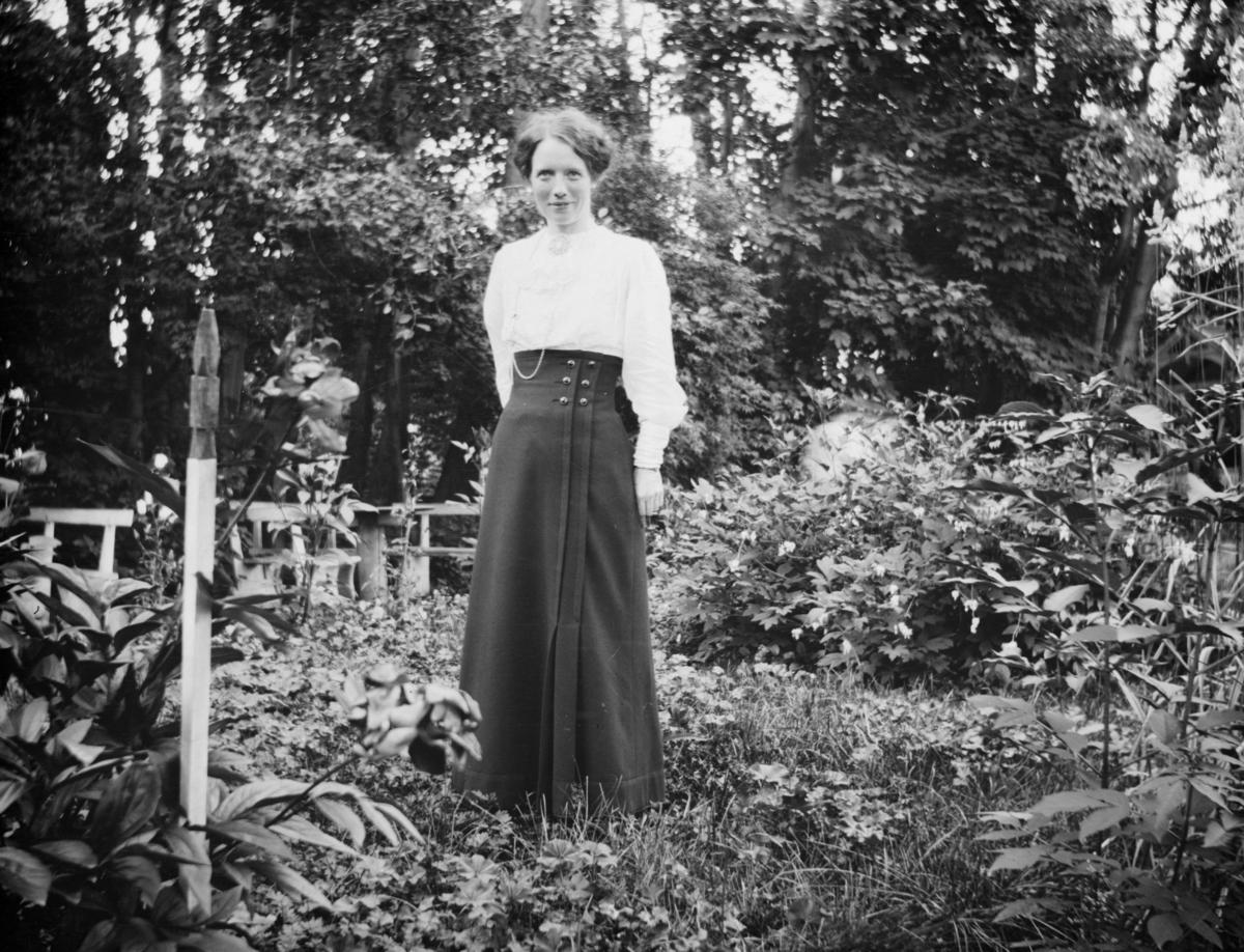Ung kvinne poserer med en hage i bakgrunnen