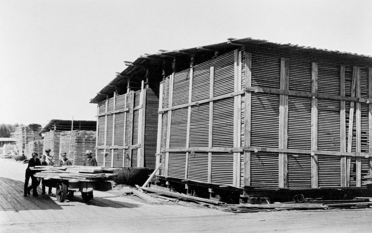 Fra bordtomtene ved et av sagbrukene som norske gründere fikk etablert i Arkhangelsk eller Onega i Nordvest-Russland mot slutten av 1800-tallet eller tidlig på 1900-tallet.  Til venstre i forgrunnen ser vi fem gutter eller unge menn, som kjørte ei tralle med jernhjul på en plattform med plankegolv.  Ved siden av ser vi store plankestaber, der nyprodusert skurlast skulle lufttørkes før den var klar for salg og utskiping, i hovedsak til vesteuropeiske markeder.  Bordstablene kvilte på støpte fundamenter av betong, plassert på rekker med et par meters mellomrom og i et mønster som innebar at ytterkantene dannet en firkant.  På disse ble det lagt kraftige, firskårne underlagsbjelker, og på dem igjen ble det lagt bord eller planker parallelt i «floer», med krysslagte «strøbord» med en viss innbyrdes avstand, som mellomlegg.  Poenget var å sikre luftsirkulasjon, og dermed tørk.    Bord- og plankestablene ble lagt med et par-tre meters mellomrom, noe som var nødvendig for å sikre framkommelighet og arbeidsrom for tomtearbeiderne som sto for stablinga.  Over de to nærmeste stablene ser vi hvordan de har fått overdekning mot nedbør i form av et slakt saltak, lagd av vrakbord.  I dette tilfellet dekte taket også over mellomrommet mellom to stabler.  I bakgrunnen ser vi andre stabler, hvorav bare en har tak.  De øvrige skulle åpenbart bygges videre oppover i høyden.