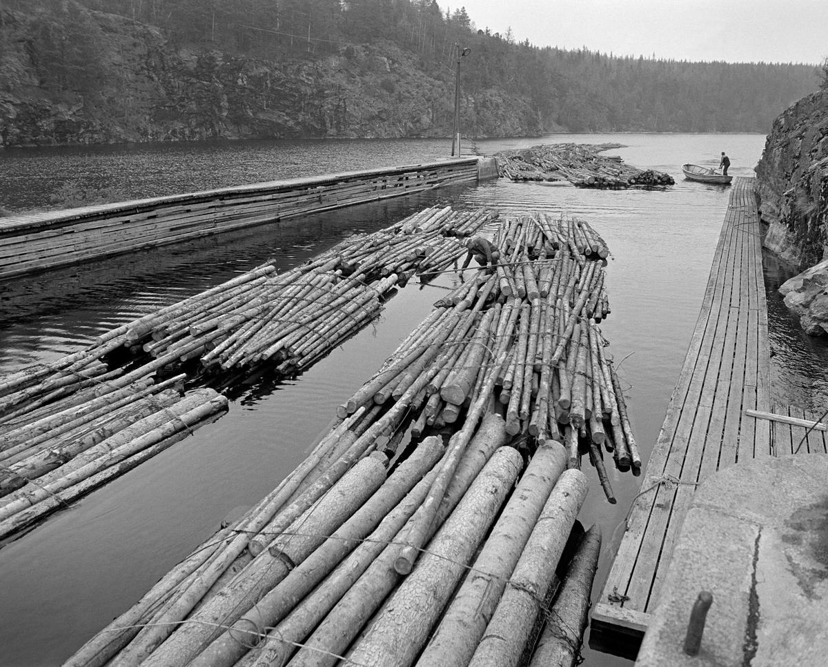 Tømmer i og ovenfor innløpskanalen til Brekke sluser i tidligere Berg herred, nåværende Halden kommune, i Østfold.  Hit ble tømmeret slept fra Strømsfoss sluse i nordenden av Aremarksjøen (Ara) via Skotsbergelva, Aspern og Stenselva.  På kraftverksdammen ble de store slepene fortøyd og delt i mindre enheter for sleping fram mot slusekanalen, deretter i enda kortere kjeder som kunne få plass i slusekamrene.  I forgrunnen ser vi inntakskanalen til sluseanlegget, omgitt av ei ganglense langs bergveggen til høyre og en høyere arbeidsplattform av tre, bygd på fjell til venstre.  Mellom disse lå det to lenker, hver med fire bunter («moser») ubarket massevirke, som skulle sluses de 26,5 høydemetrene ned i Brekkeelva, hvor det kunne slepes videre mot og over Femsjøen.  En mann satt på huk med fløterhaken sin på ei av disse slusevendingene da dette fotografiet ble tatt.  I bakgrunnen ser vi en åpen varpebåt av stål som var i ferd med å vende etter å ha slept mer tømmer mot kanalinnløpet.  En liten historikk om tømmerfløting og kanaliseringsarbeid i Haldenvassdraget finnes under fanen «Opplysninger».