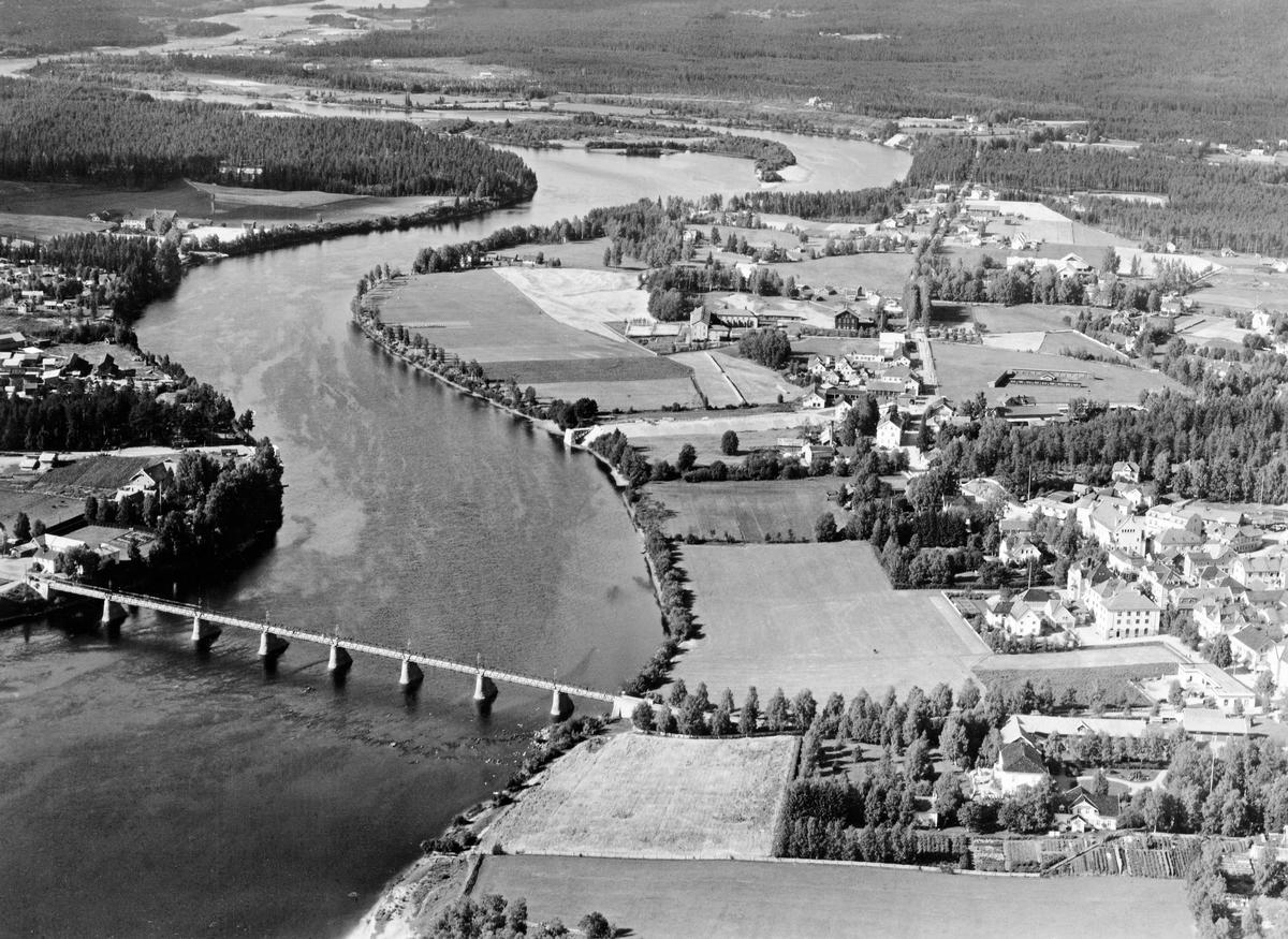 Flyfotografi, tatt over kommunesenteret i Elverum sommeren 1935.  Vi ser Glomma, som bred og stilleflytende slynger seg fra Strandbygda og sørover.  På vestsida av elva ser vi noe av bebyggelsen på Vestad.  Nord for denne skimter vi Elverum dampsag og noe av jordvegen på garden Grindalen.  På østsida av elva ser vi tunet på Gårder (opprinnelig «Alfarheimr», som ble til prestegjelds- og kommunenavnet Elverum), omgitt av hage og åkrer.  Arealene videre oppover langs elva ble fortsatt brukt til jordbruksformål, mens bebyggelsen i kommunesenteret Leiret var samlet langs vegen som gikk nord-sør (Storgata), med en liten konsentrasjon omkring Festivitetslokalet og hotellet, der også St. Olavsgate hadde urban bebyggelse.  Mye av dette ble ødelagt under bombinga av Elverum i 1940.  Den nordligste delen av Leiret, med blant annet Folkvang skole (1876) og Elverum lærerskole (1924) ble imidlertid spart fra ødeleggelsene.  Svært framtredende på bildet er «Gammelbrua», som ble bygd i 1862 med forventning om at en mellomriksbane fra Hamar skulle krysse Glomma her med spor videre i retning Trysil og Sverige.  Denne jernbaneplanen ble aldri realisert, men brua fikk vegtrafikk og ble en viktig forutsetning for tettstedsutviklinga i Leiret.  I mellomkrigstida vokste trafikken, som også i stadig større omfang ble motorisert.  Dermed ble det behov for nok ei bru.  Etter langvarige diskusjoner ble det bestemt at det skulle reises ei hengebru et par hundrede meter nord for den første brua, med vegtrasé (i dag Lundgårdvegen) videre østover i sørenden av mart'nsplassen, som etter hvert ble utviklet til et torg.  Dette fotografiet viser hvordan man med veger mot et nye brustedet, både fra vest og øst.  «Nybrua» sto imidlertid ikke ferdig før året etter at dette bildet ble tatt, i 1936.