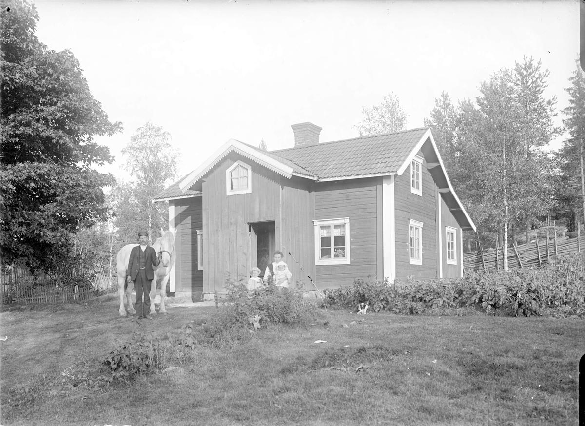 Familjen Åhlén framför nybyggartorpet Nybo, Smedsbo 1:5, Tärna socken, Uppland, sannolikt sommaren 1915