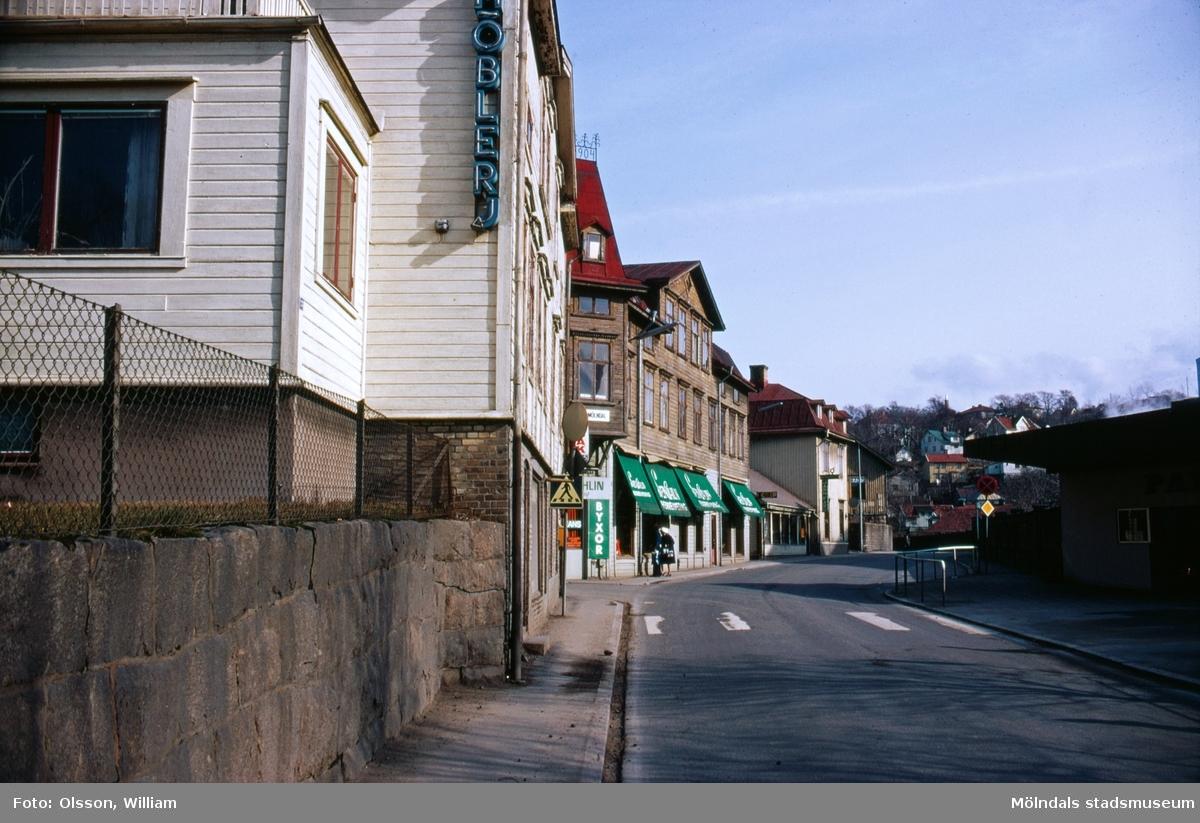 Till vänster ses Eneborgs på Kvarnbygatan 23. Bortanför detta ligger Kvarnbygatan 25, Sven Ahlins Herrekipering. Till höger ligger huvudentrén till Papyrus industriområde. Okänt årtal.
