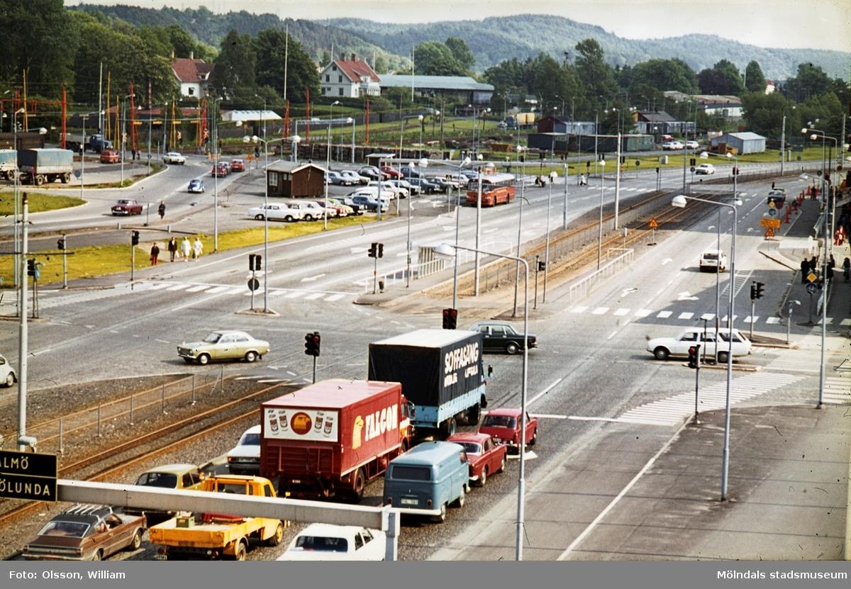 Vy åt söder över Mölndals centrum, okänt årtal. Till höger ser man en bil köra från Tempelgatan ut på Göteborgsvägen. Längre bort ser man dåvarande järnvägsövergången mellan centrum och Kvarnbygatan (senare Mölndals bro) samt Forsåker.
