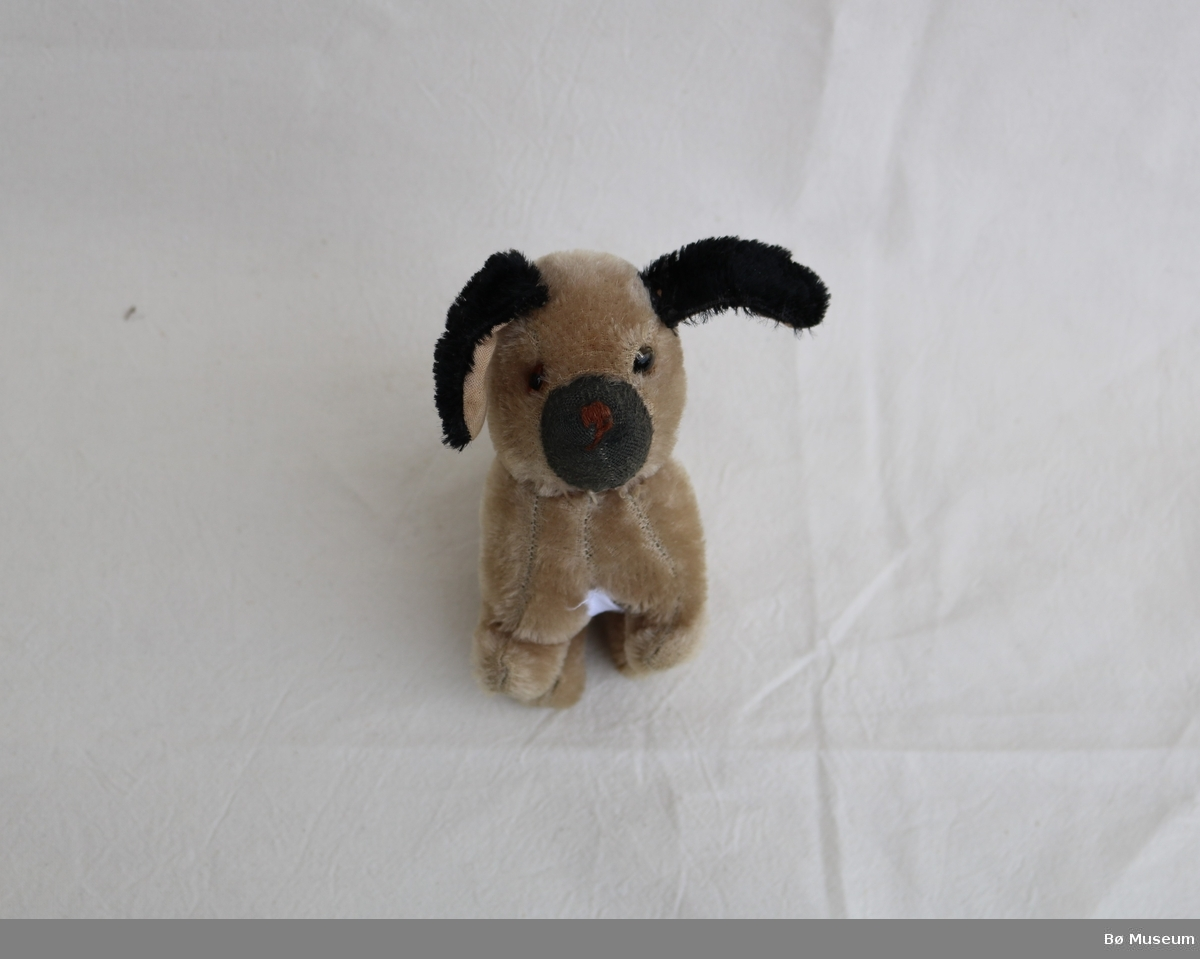 Kosedyr i form av ein hund. Hovudet og ørene er sydd på for hand etter å ha vore rive av. Brodera snute. Påsyddde glasøyne.