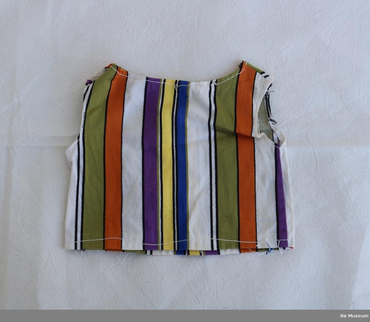 Bluse til dokke med lomme på magen og to trykknappar på venstre skuldere. Utan armar. Noko ujamn saum i fall nede , rundt armane og i halsen. Blusa er sauma i eit stripete stoff. Stripene har ulik breidde og fargar.