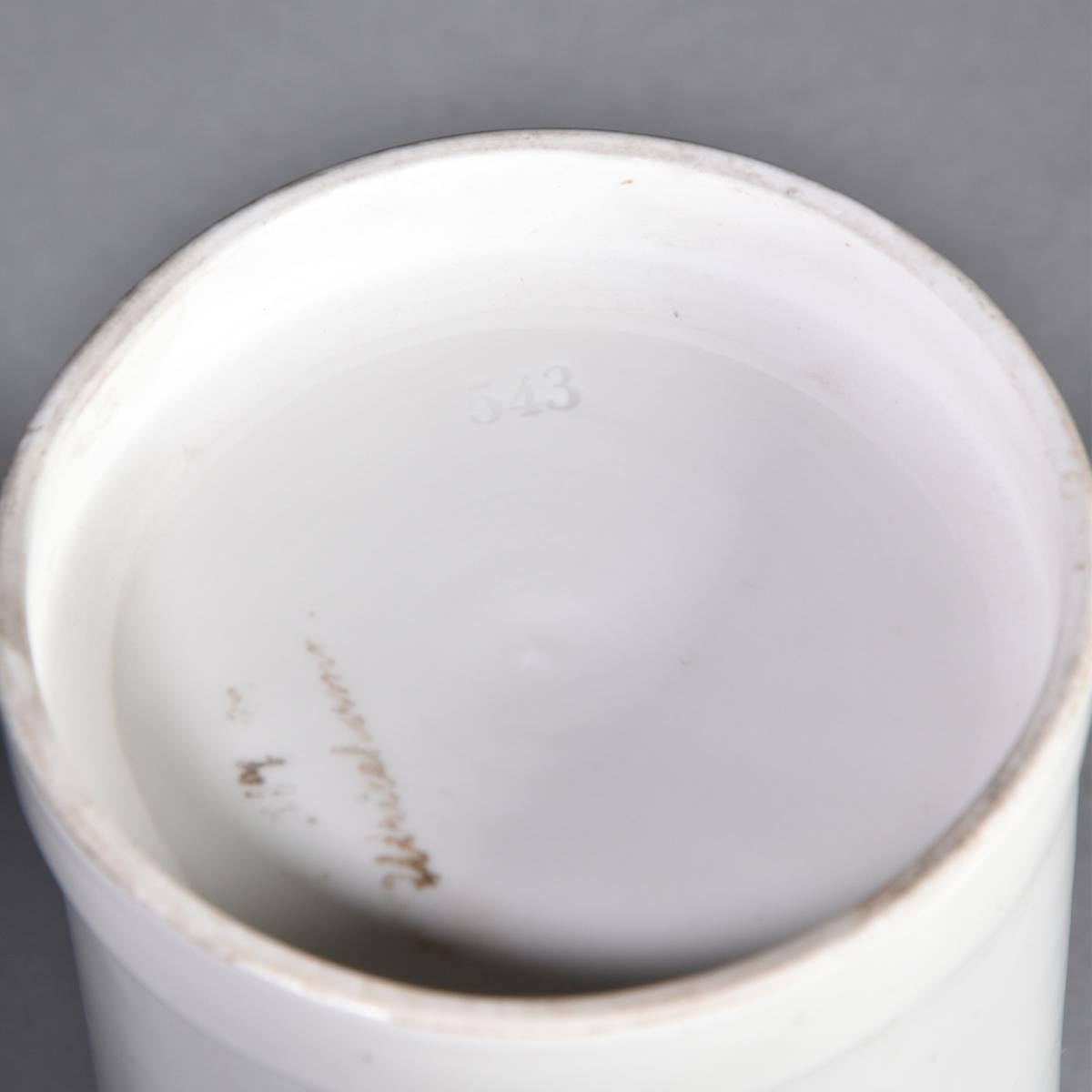 Ståndkärl, apoteksburk, av vitt porslin, cylindriskt med plant lock. Svart text inom guldfärgad lagerkrans krönt av krona.