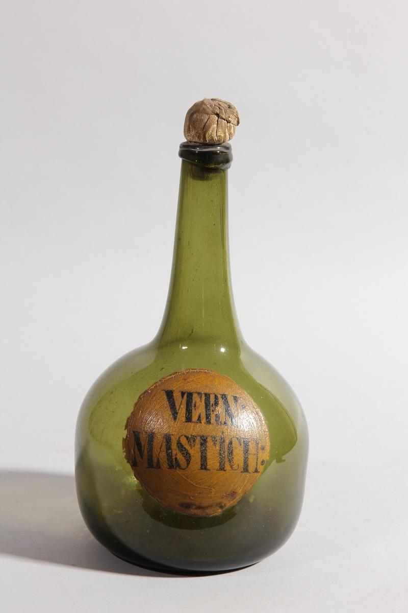 Flaska av grönt glas med skinnombunden kork. Rund med flat botten och lång hals.