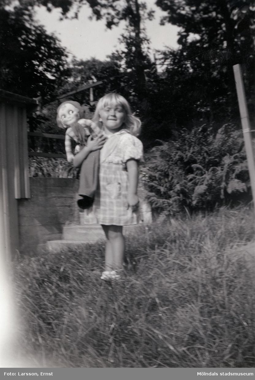 """""""Berit och dockan Ingrid, 1939"""". Berit Gustafsson med sin trasdocka i famnen. Platsen är """"Stusshålan"""", Kryssgatan i Mölndal."""