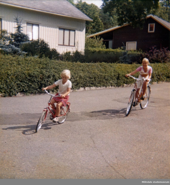 """Systrarna Christine och Ingela cyklar på vändplanen i """"Stusshålan"""" på Kryssgatan i Mölndal. På den här gatan lärde sig Christine att cykla. Ca 1976."""