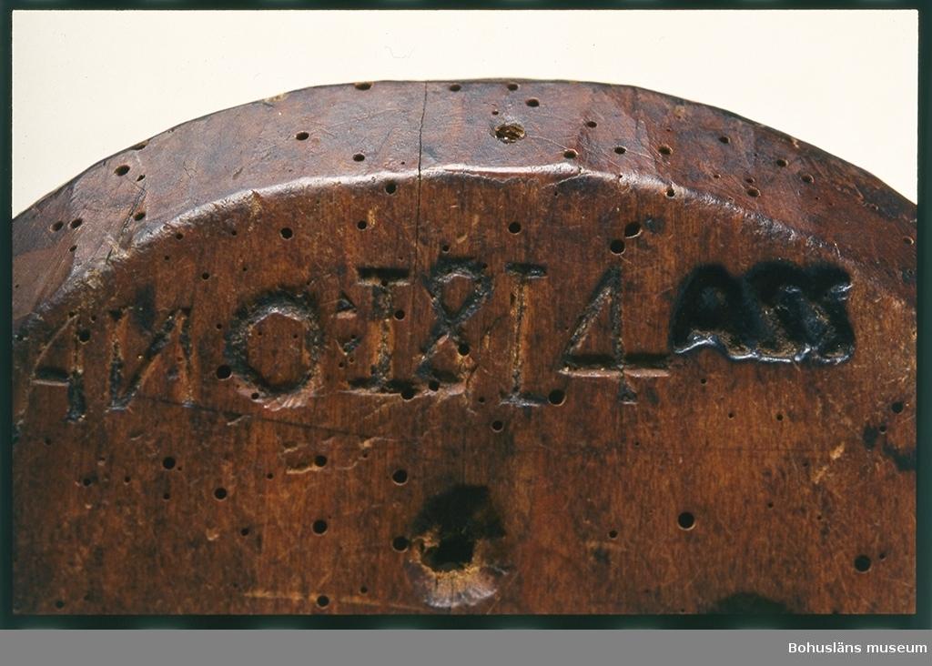 """Skuren i ett stycke, sju genomgående hål där vasslan rann ut.  Märkt: """"ANO 1814"""" """"ASS"""". Maskäten samt två större angrepp på kanten. Geometriskt mönster i form av hjul i mitten med två nivåer av blom-/stjärnmönster runtom. Karv- och uddsnitt.  Ur handskrivna katalogen 1957-1958: Ostform, """"ANO"""", """"ASS"""". D. c:a 20, H. c:a 6 cm; skuren ur ett enda trästycke; 7 genomg. hål; Maskäten och ngt trasig."""