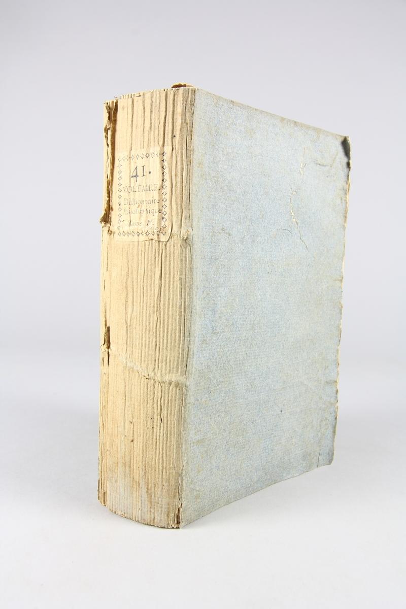 """Bok, pappband,""""Oeuvres complètes de Voltaire.""""  del 41, tryckt 1785. Pärm av gråblått papper, på pärmens insidor klistrade sidor ur annan bok. Med skurna snitt. På ryggen pappersetikett med tryckt text med volymens namn och nummer. Ryggen blekt."""