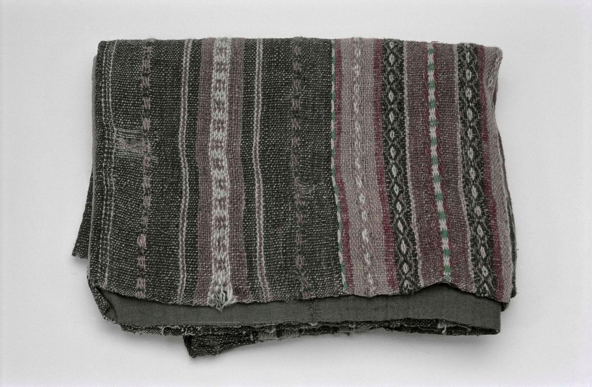 Täcke. Högertvinnat lingarn i varpen, 37 trådar på 10 cm. Inslag av vänsterspunnet hårgarn i svart, lila, rosa, grönt, blått och vitt. Anilinfärger. I två våder.