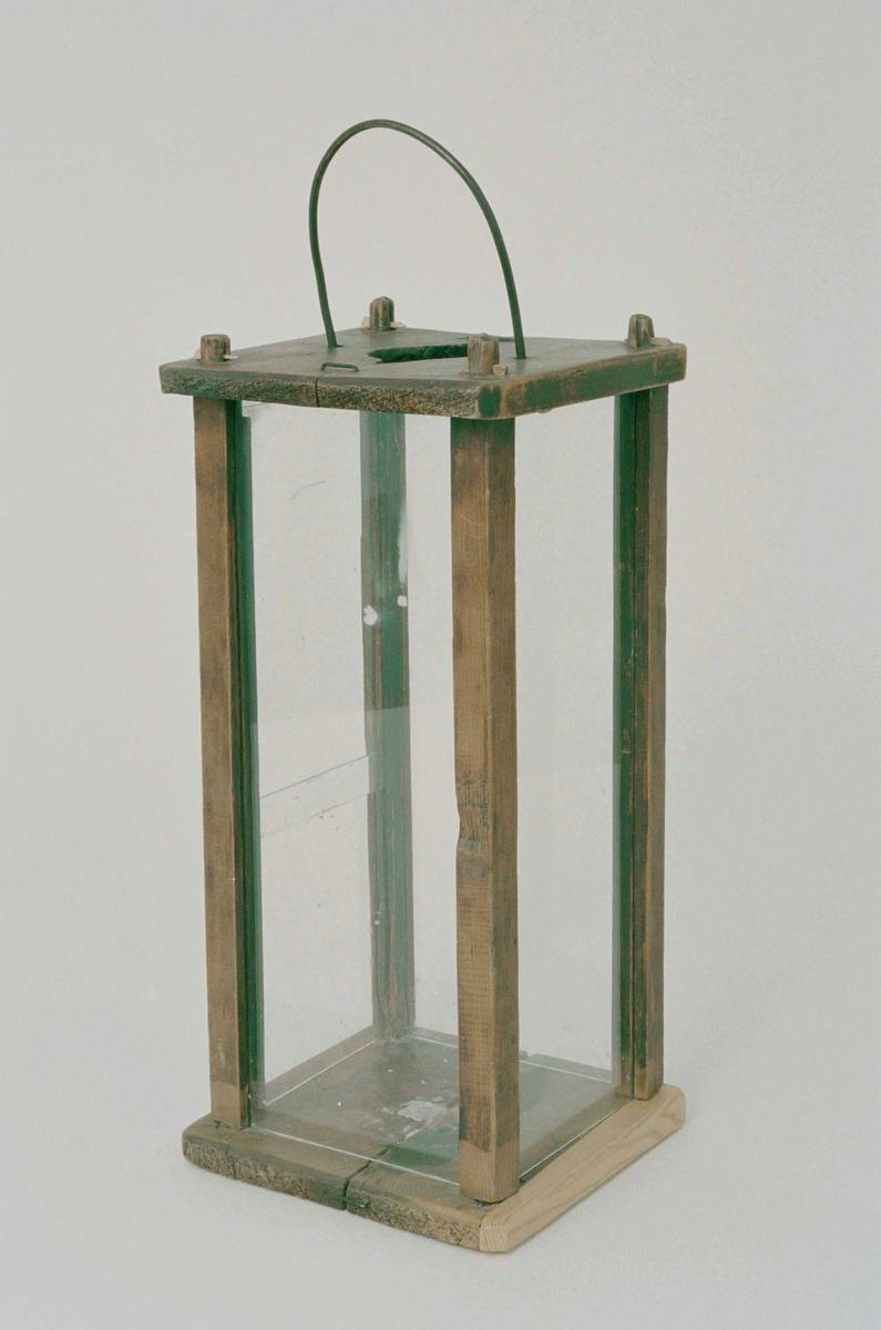 Fyrkantig lykta med hörnstolpar och bottnar av trä,brunbetsad, sidorna av glas. En sida har delad glasskiva, skjutbar i vertikalt läge. Handtag av järn, ljuspipa saknas.