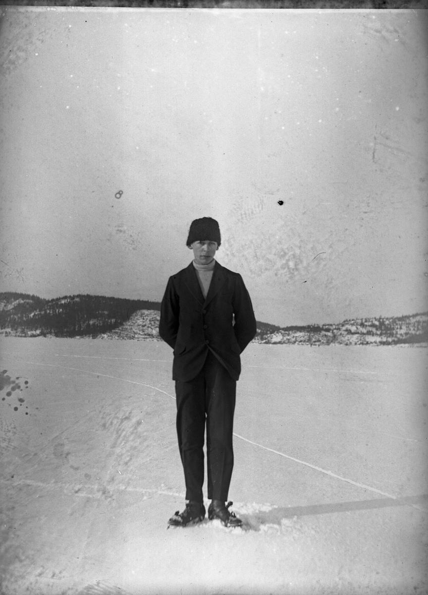 Hugo Larsson fotograferad vid en skridskofärd på Mjörn. Hugo bär svart sportkostym, svart mössa och ljus polo. Sjön är täckt av snö.