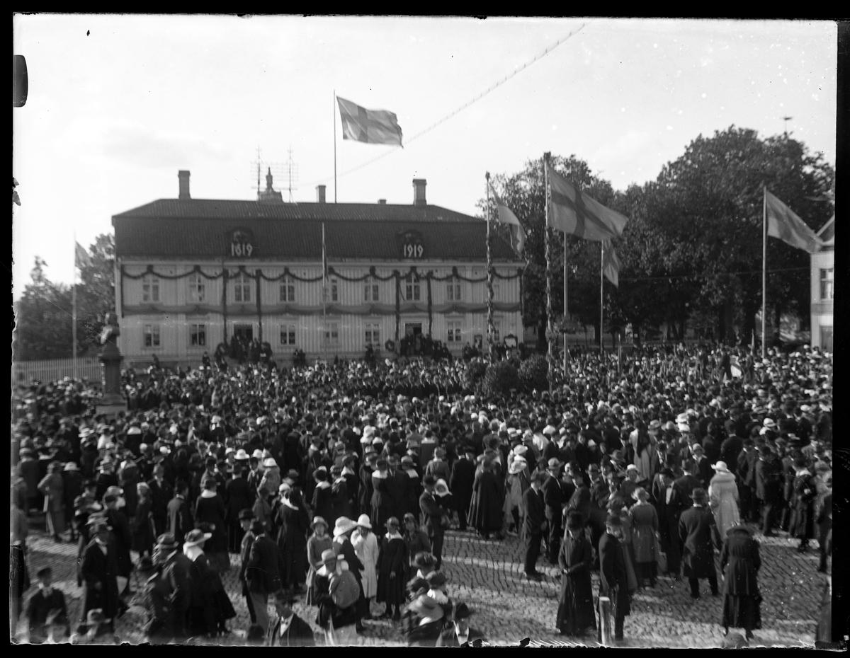 Folksamling på Stora torget för att fira Alingsås stads 300års jubileum. I bakgrunden syns Rådhuset dekorerat med lövgirlanger.