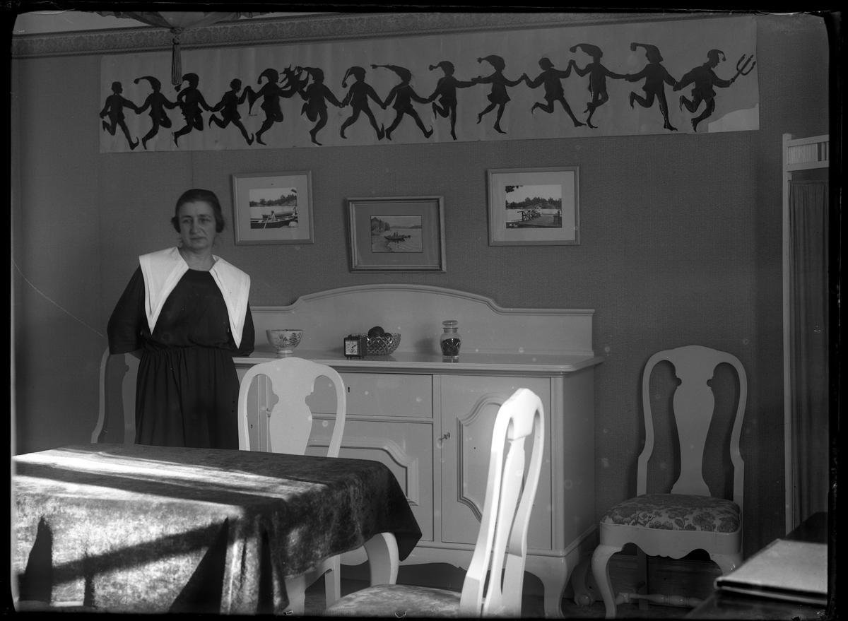 Anna Lenander står lutad mot en vit skänk i en matsal. På väggen hänger en pappersbonad med tomtenissar i dans.