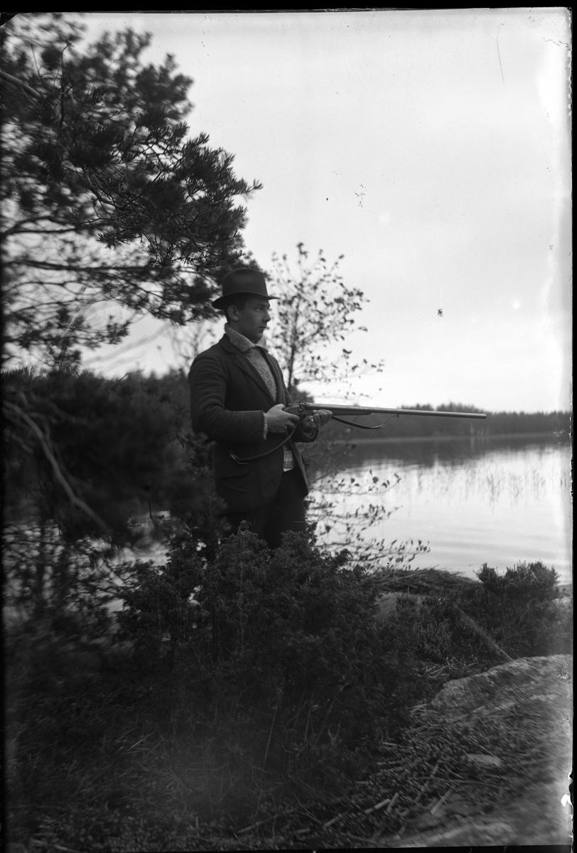 Fotografen själv på andjakt vid Norseskären. Han är klädd i stickad tröja, kavaj och hatt och i händerna håller han en bössa.