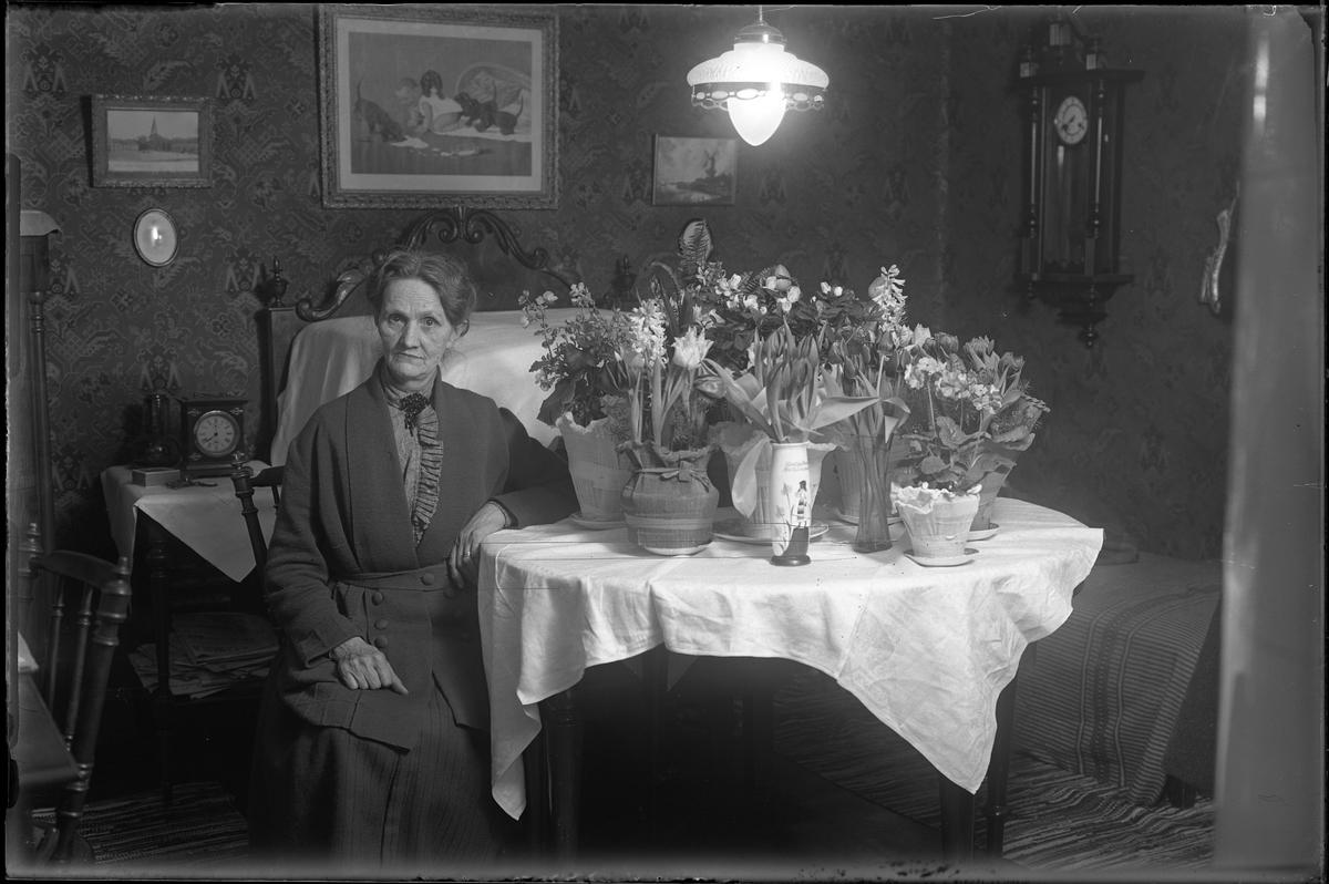 Porträtt av Fru Nordgren, förmodligen i samband med en jämn födelsedag med tanke på blommorna på bordet bredvid henne.
