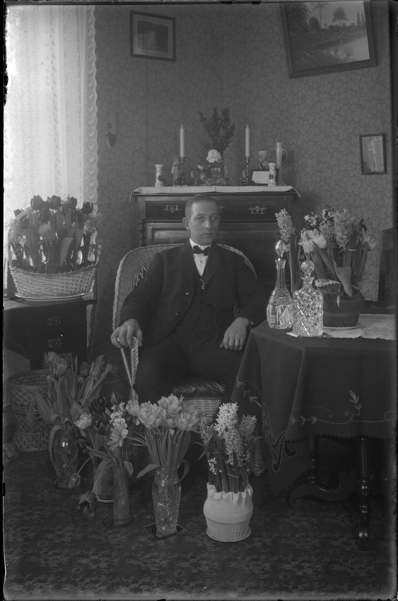 Porträtt av Carl Dahl sittandes i en korgstol. Förmodligen är bilden tagen i samband med en jämn födelsedag med tanke på blommorna som står runt honom.