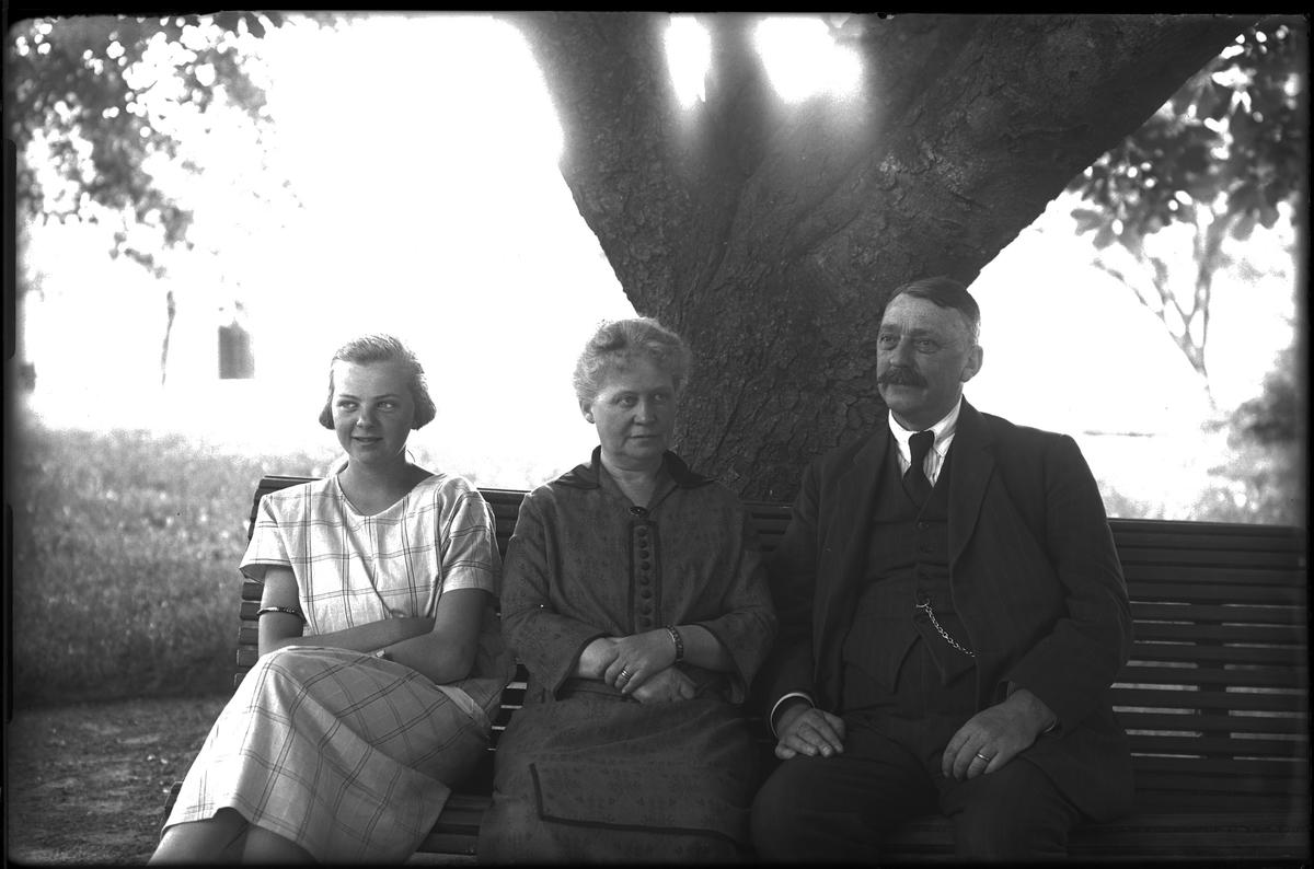 """Två kvinnor, en yngre och en äldre sitter på en bänk under ett träd. Bredvid dem sitter en kostymklädd man. I fotografens egna katalog står det """"Sandsten med familj""""."""