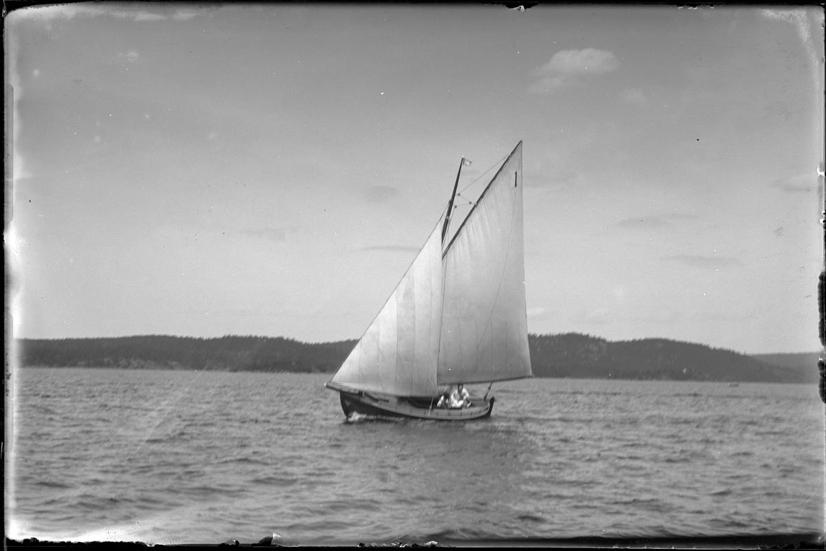 "Segelbåten ""Aina"" ute på sjön. Ombord syns två personer."