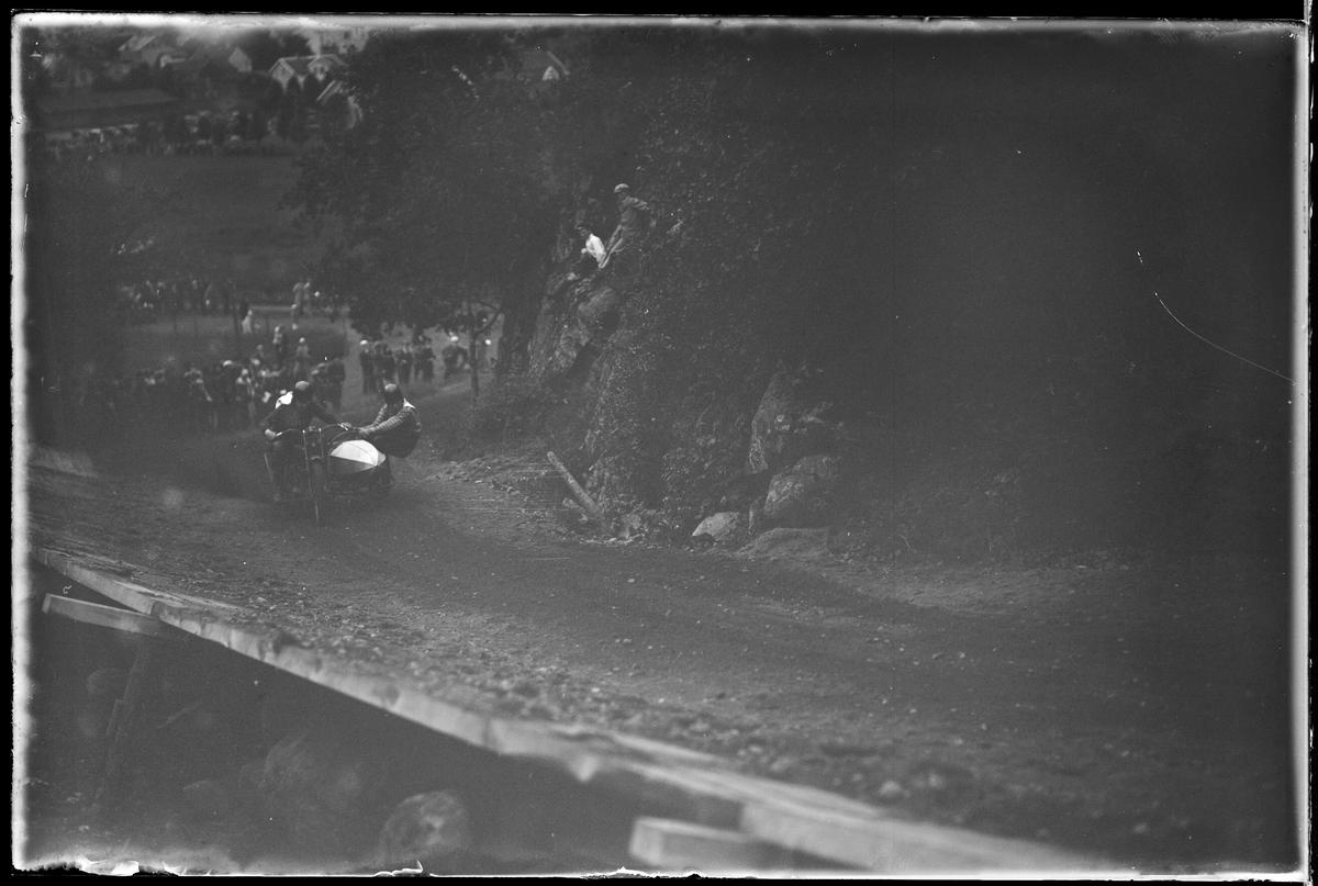 """En person kör en motorcykel upp för en backe medan en annan person hänger ut från sidovagnen. I bakgrunden skymtar åskådare. I fotografens egna anteckningar står det """"A.M.Ks [Alingsås motorklubb] backtävlan"""""""