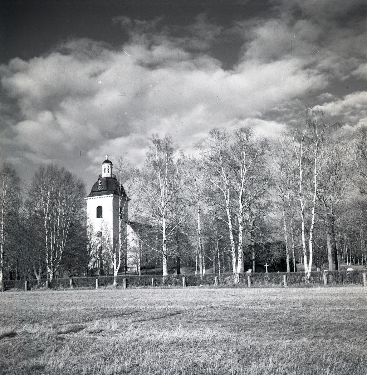 Färila kyrka bortom ett fält av åkermark.