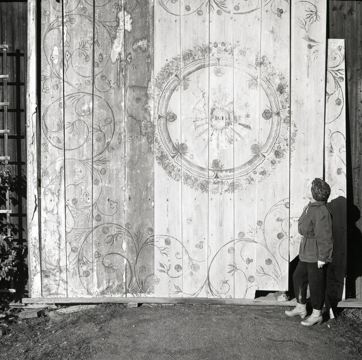 En kvinna står intill ett innertak vilket är lutat mot en vägg, 1968-1969.
