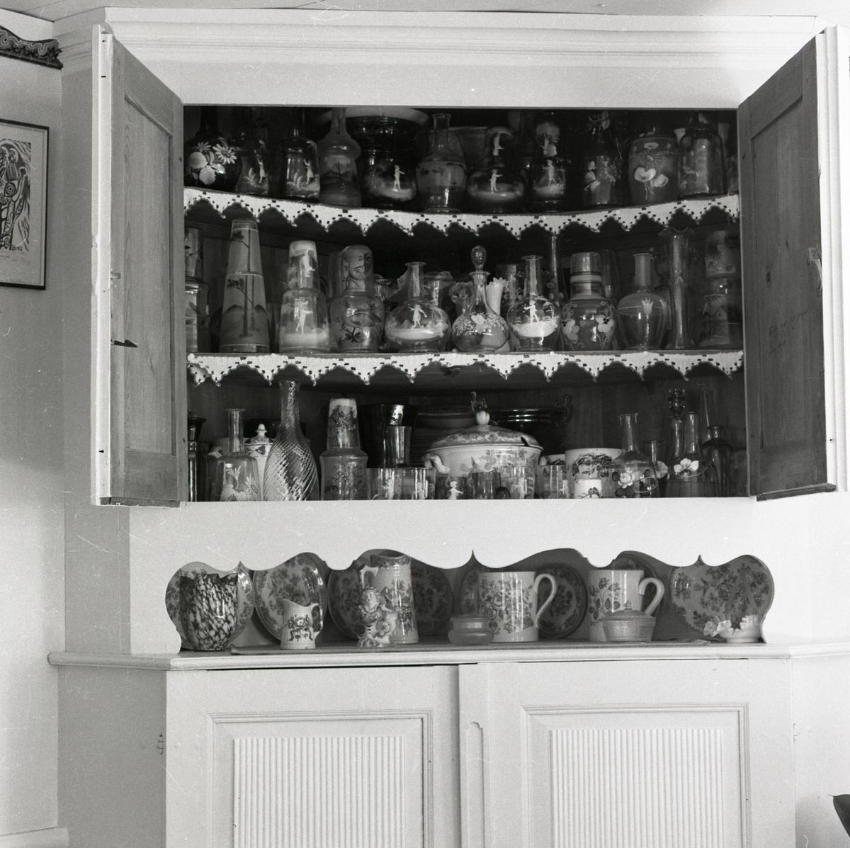 Ett hörnskåp fyllt med glasföremål vid gården Sunnanåker, 1973.