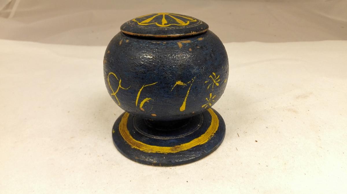 Form: Kuleforma 1 kuleformet æske.  Dreiet kuleformet æske med laag. I samme stykke er dreiet en vid stet (diameter 10 cm) paa kort stilk. Kulens diameter 10 cm, æskens høide 10,8 cm. Æsken blaamalt med gule forsiringer, rundt midten malt: M.N.S.M. 1867. Kjøpt av Olaf L. Mørkri, Skjolden.