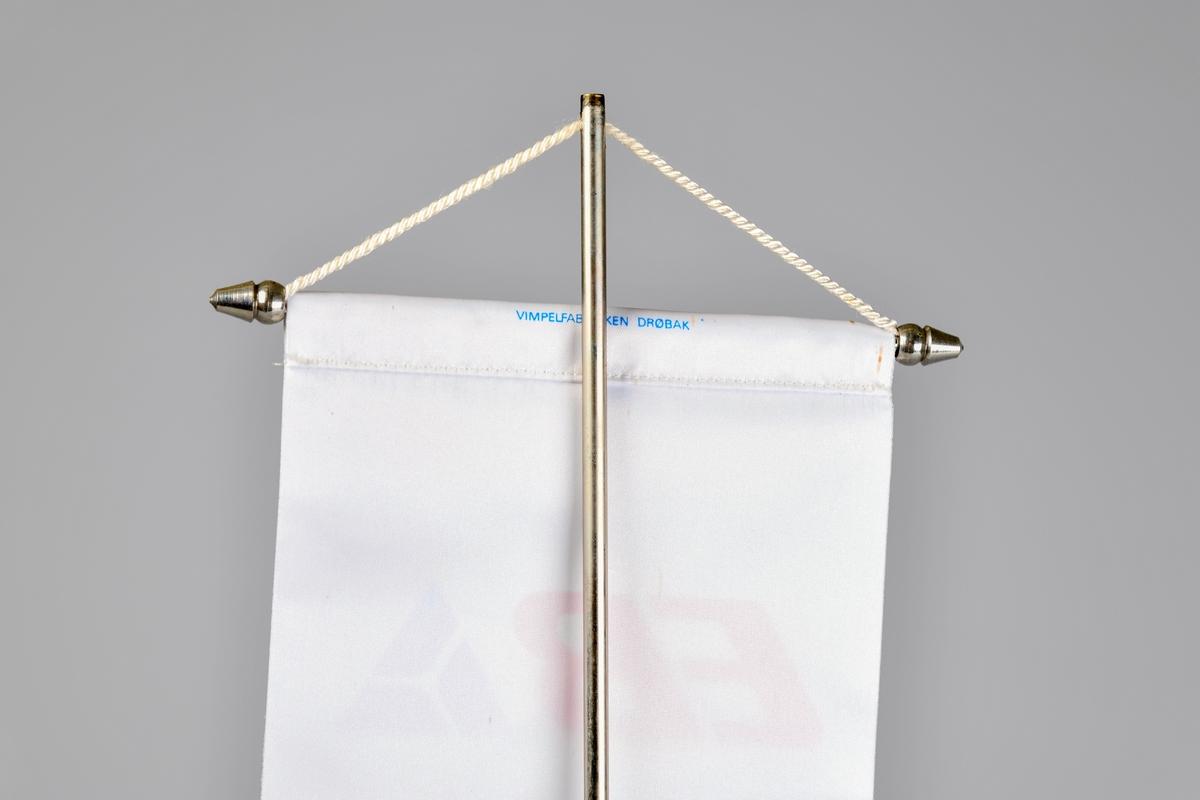Bordvimpelen er rektangulær. Overkanten er omsydd, og en metalltang med kjegleformede avslutninger er stukket gjennom. EVed vimpelens underkant er det påsydd et hvit frynsebånd. Det er kun en side av vimpelen som har logo påtrykket.  Den hvite tråden øverts på vimpelen brukes til å henge den i et bordstand bestående av et sølvfarget metallstang som er skrudd fast i en rund fot. Grønn filt limt på undersiden. Mulgens en toppdel som holder tråden på plass som er forsvunnet.