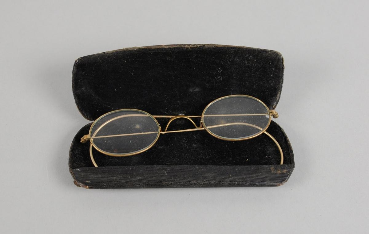 Svart brilleetui av metall med svart fór. Etuiet er slitt. I etuiet ligger det et par briller.