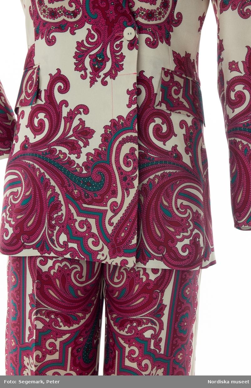 """Kavaj av polyester med tryckt mönster i rött och grönt på vit botten. Bland annat paisley-mönstrad. Kavajen har slag och nedvikt krage. Två framstycken och två bakstycken. Framstycken med dubblerat tyg. Var framstycke med ett insnitt i midjan och ficka med ficklock. Ficksömmarna ej uppsprättade. På vänster framstycke tre tygklädda knappar, motsvarande tre knapphål på höger framstycke.  Bakstyckena fodrade med vitt syntettyg. Framstyckena endast fodrade med smal remsa vid framstyckenas sidsömmar. Fickpåsar av samma tyg. Vänster framstycke med innerficka med knapp. Ärmarna fodrade med vitt tyg med svart rand. Lätt vaderad vid axlarna. Hank av ljust läder med text """"WHYRED"""" i nacken. Etikett på insidan av vänster framstycke med text """"WHYRED"""" samt storleksangivelse """"36"""" och """"MADE IN CHINA"""". /Leif Wallin 2018-08-27"""
