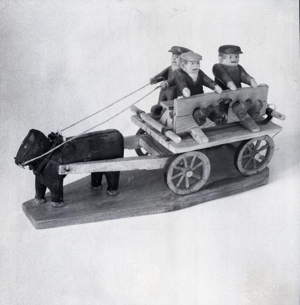 En modell föreställande tre figurer på en vagn som blir dragen av en häst.