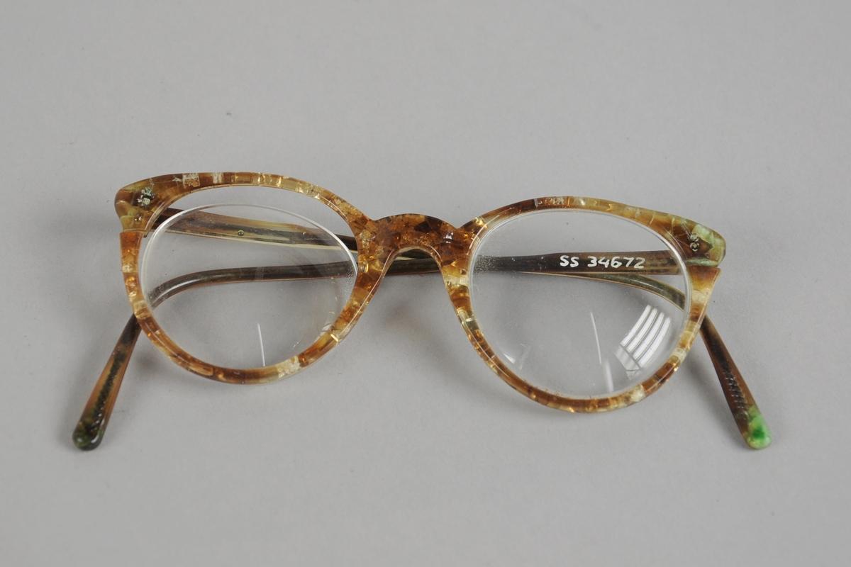Briller med runde brilleglass og plastinnfatning. Plasten er i ferd med å smuldre opp.